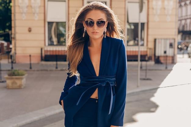 Retrato de mulher sexy e elegante andando na rua com um terno azul e óculos escuros em um dia ensolarado de outono