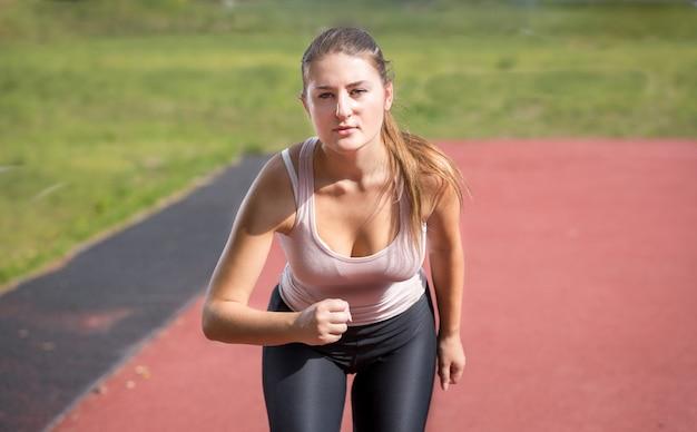 Retrato de mulher sexy magro correndo no estádio em dia de sol
