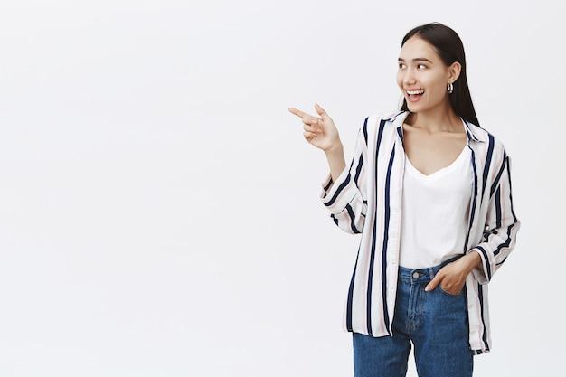 Retrato de mulher simpática e bonita em jeans e blusa listrada estilosa, segurando a mão no bolso, apontando e olhando para a esquerda com um largo sorriso