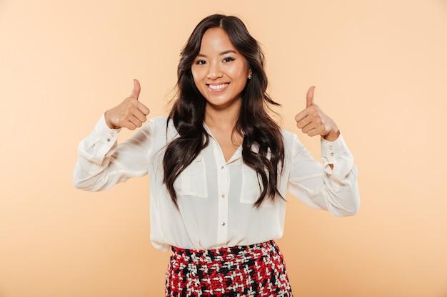 Retrato de mulher sincera asiática em casual, olhando para a câmera, mostrando os polegares para cima gesticulando como sinal sendo isolado sobre fundo pêssego