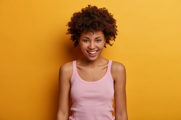 Retrato de mulher sincera bonita parece positivamente, tem sorriso dentuço, olhar direto, pele saudável, vestida com roupa casual, isolada sobre a parede amarela. emoções felizes