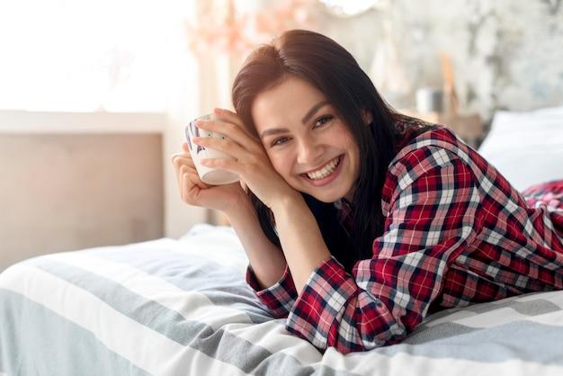Retrato de mulher sorridente, aproveitando a manhã na cama