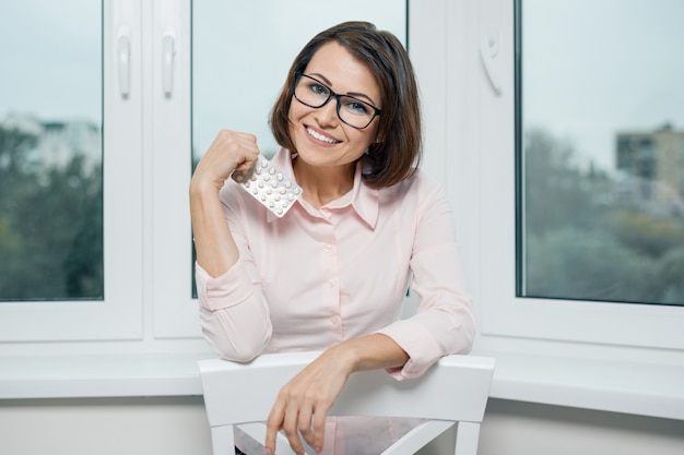 Retrato de mulher sorridente com blister de comprimidos