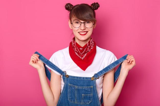 Retrato de mulher sorridente com cachos engraçados, veste camiseta, macacão jeans e bandana no pescoço, tem sorriso
