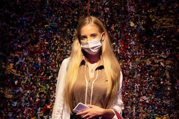 Retrato de mulher sorridente com máscara contra a parede.