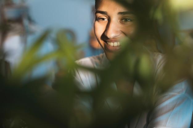 Retrato de mulher sorridente com planta turva