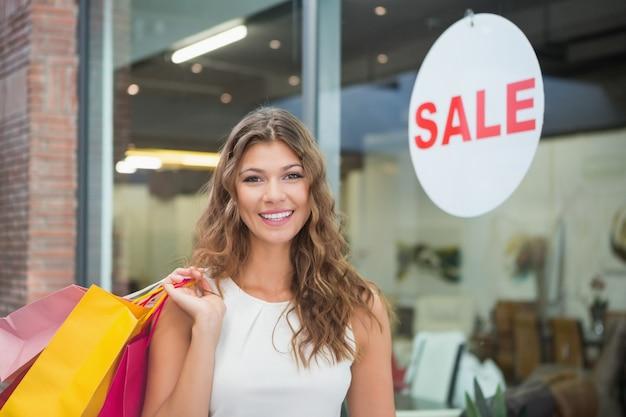 Retrato de mulher sorridente com sacolas de compras olhando câmera