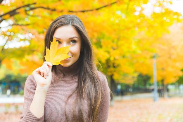 Retrato de mulher sorridente com uma folha amarela no outono