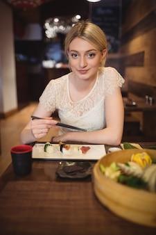 Retrato, de, mulher sorridente, comer sushi