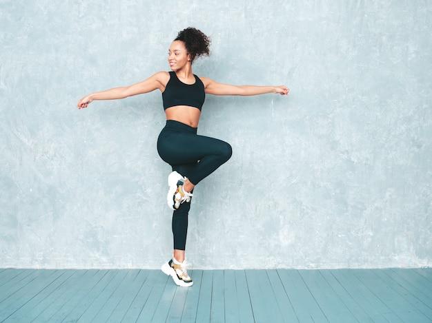 Retrato de mulher sorridente de fitness em roupas esportivas com penteado de cachos afro