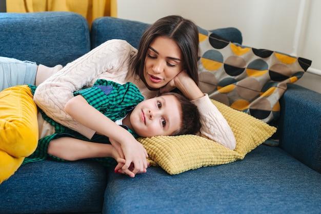 Retrato de mulher sorridente e criança deitada no sofá. família fofa é feliz e parece perfeita