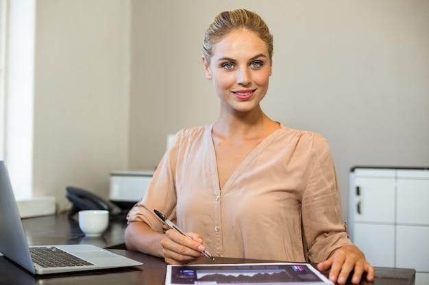 Retrato de mulher sorridente, escrevendo no documento no escritório