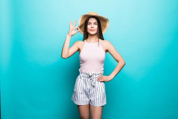 Retrato de mulher sorridente feliz usando vestido, chapéu de palha de verão mostrando gesto ok, polegares sinalizam cópia espaço isolado na parede azul ... emoções sinceras de pessoas, conceito de estilo de vida. área de publicidade