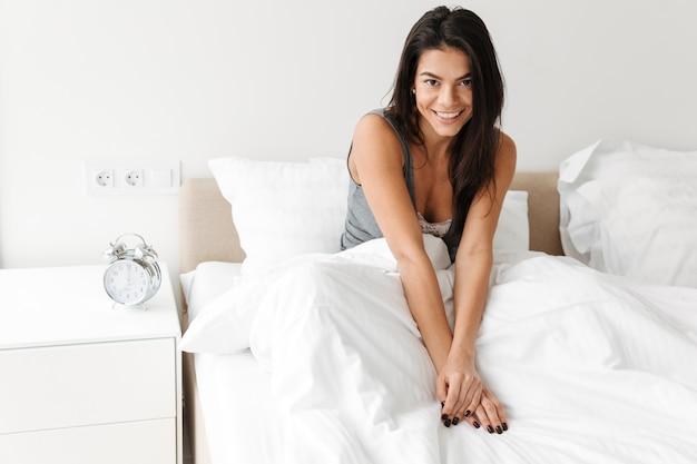 Retrato de mulher sorridente fresca, descansando na cama depois de dormir com roupa limpa branca no quarto e olhando para a câmera