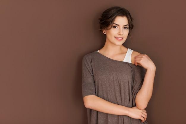 Retrato de mulher sorridente na parede marrom