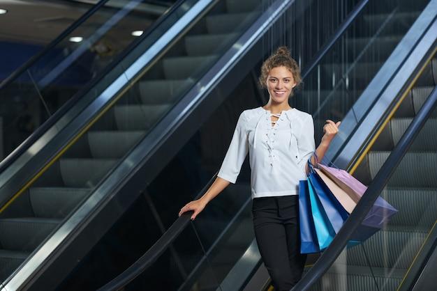 Retrato de mulher sorridente, olhando para a câmera e posando na escada rolante no shopping