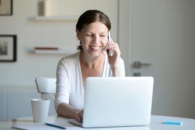 Retrato de mulher sorridente perto de laptop falando ao telefone.