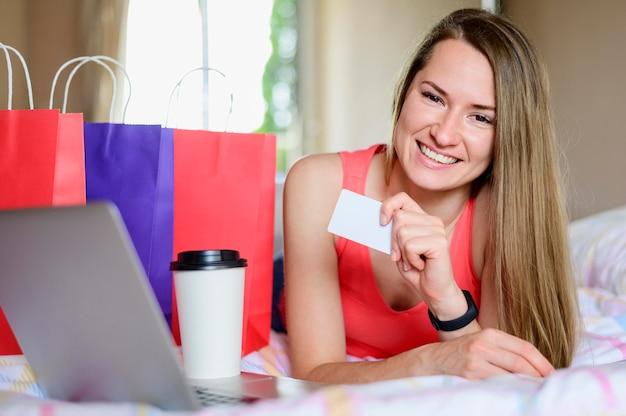 Retrato de mulher sorridente posando com sacos de compras
