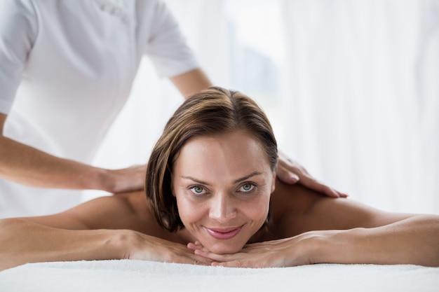 Retrato de mulher sorridente, recebendo massagem nas costas