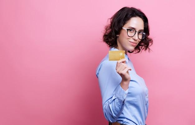 Retrato, de, mulher sorridente, segurando, cartão crédito, em, mão, e, olhando câmera, isolado, ligado, cor-de-rosa