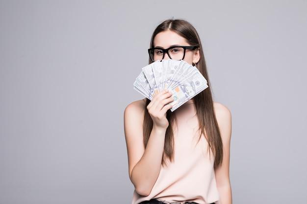Retrato de mulher sorridente segurando dólares isolados sobre parede cinza