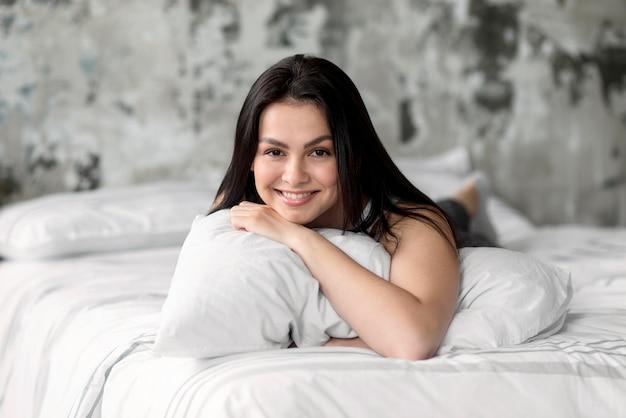 Retrato, de, mulher sorridente, segurando travesseiro
