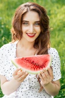 Retrato de mulher sorridente, segurando uma fatia de melancia.