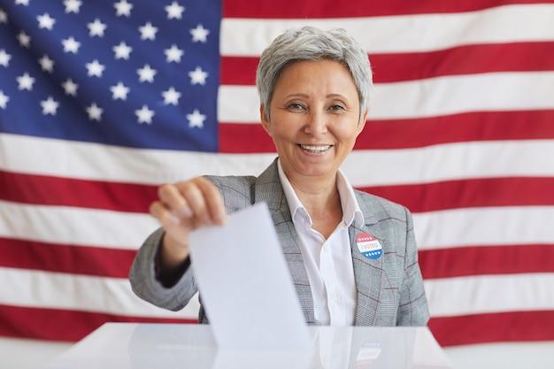 Retrato de mulher sorridente sênior colocando boletim de voto nas urnas e enquanto posava contra a bandeira americana no dia da eleição, copie o espaço