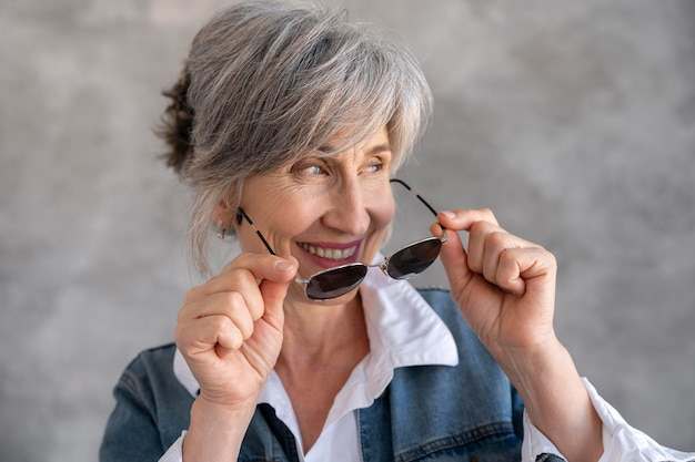 Retrato de mulher sorridente sênior com óculos de sol