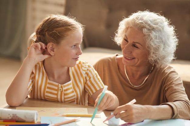 Retrato de mulher sorridente sênior, olhando para uma linda garota ruiva e desenhando juntos enquanto estão sentados no chão, perto da mesa de café, na acolhedora sala de estar.