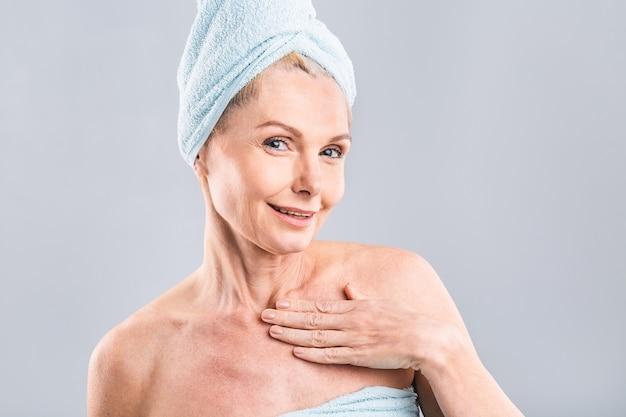 Retrato de mulher sorridente sênior, sentindo a pele macia com a mão após o banho de spa. mulher madura envolta em uma toalha no corpo e cabelo molhado, olhando para a câmera