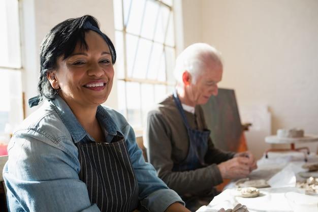 Retrato, de, mulher sorridente, sentando, por, homem, fazer, produto argila