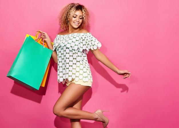 Retrato de mulher sorridente shopaholic linda segurando sacos de papel coloridos