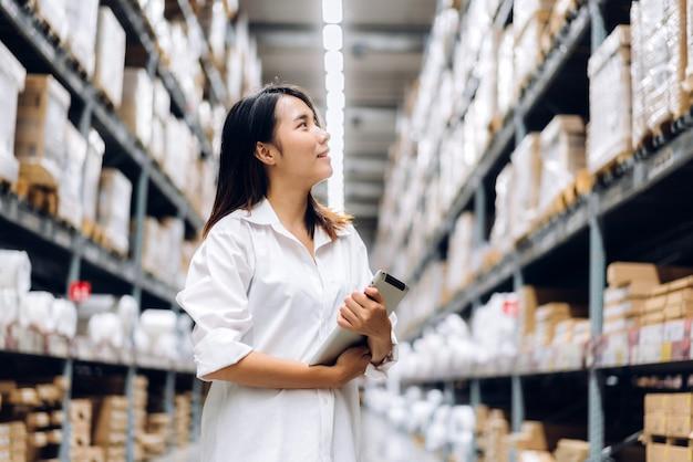 Retrato de mulher sorridente trabalhador gerente asiático em pé e detalhes do pedido no computador tablet para verificar mercadorias e suprimentos nas prateleiras com fundo de mercadorias no armazém