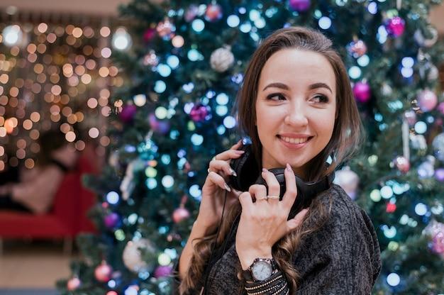 Retrato de mulher sorridente usando fones de ouvido perto da árvore de natal, olhando para longe