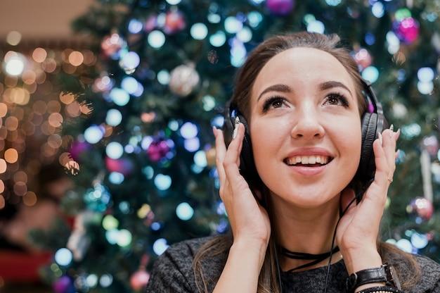 Retrato de mulher sorridente usando fones de ouvido perto de árvore de natal