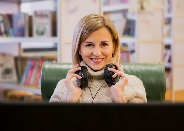 Retrato de mulher sorridente usando fones de ouvido