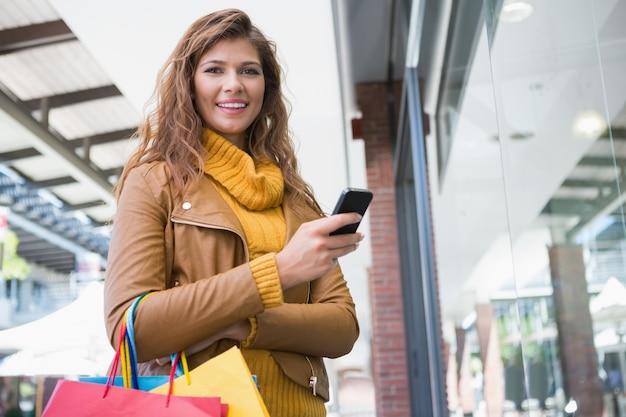 Retrato de mulher sorridente usando smartphone e olhando câmera