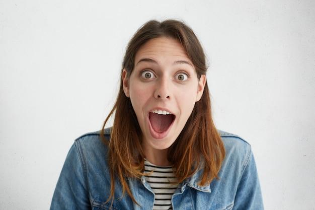 Retrato de mulher surpresa com olhos esbugalhados e boca aberta, sentindo-se chocada ao ser expulsa da universidade.