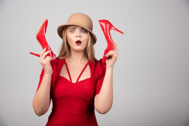 Retrato de mulher surpresa com um par de saltos.