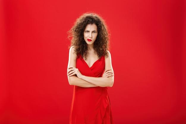 Retrato de mulher temperamental pensativa intensa com penteado encaracolado franzindo a testa, sorrindo, olhando por baixo da testa, cruzando os braços contra o peito em pose ofendida e defensiva sobre o fundo vermelho.