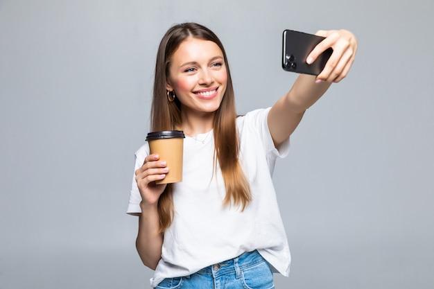 Retrato de mulher tirando foto de selfie em smartphone no escritório e bebendo café para viagem em copo plástico isolado