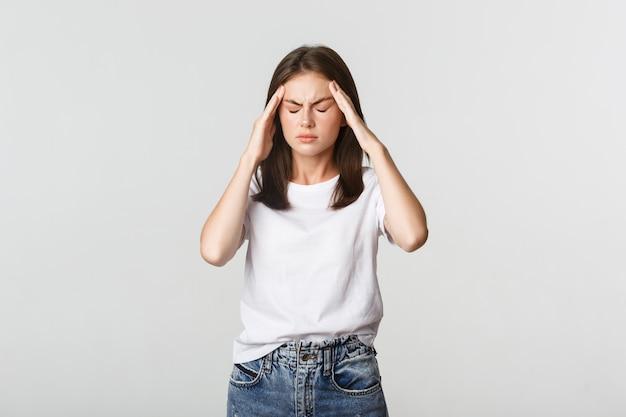 Retrato de mulher tonta ou doente, tocando a cabeça e fazendo caretas de dor, dor de cabeça, enxaqueca.