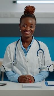 Retrato de mulher trabalhando como médica em escritório em clínica de saúde