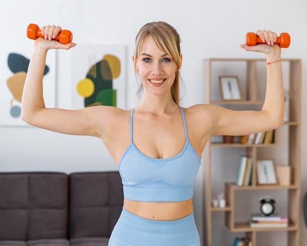 Retrato de mulher treinando em casa com pesos