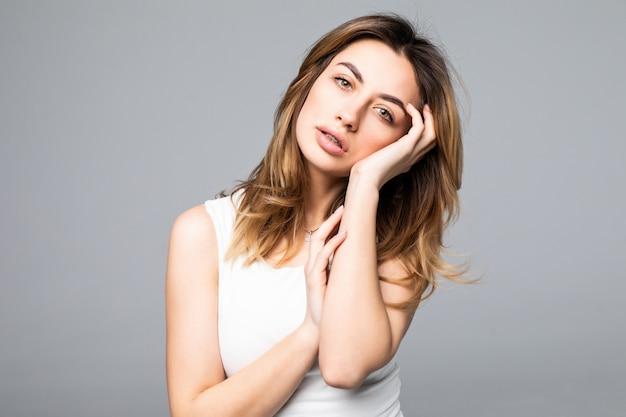 Retrato de mulher triste e chateada na camisa com dor de cabeça, estresse, problemas, tocar os templos com os dedos e fechar os olhos, de pé sobre a parede cinza