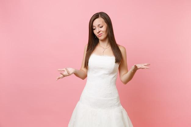 Retrato de mulher triste e culpada em lindo vestido de renda branca em pé e espalhando as mãos