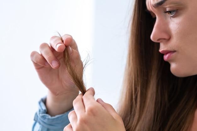 Retrato de mulher triste infeliz chateado com mecha danificada do cabelo que sofre de cabelo seco e pontas duplas.