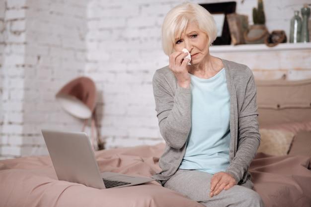 Retrato de mulher triste sênior, sentado na cama e limpando o nariz com o guardanapo.