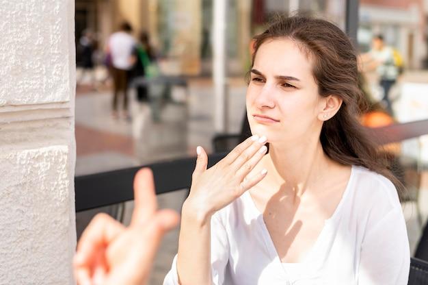 Retrato de mulher usando a linguagem de sinais para se comunicar